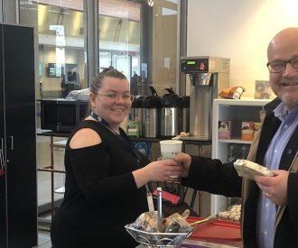 Woman handing coffee to smiling gentleman